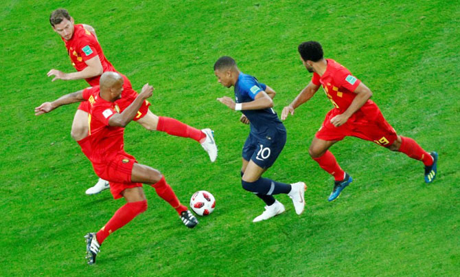 France's Kylian Mbappe is challenged by Belgium's Vincent Kompany and Mousa Dembele