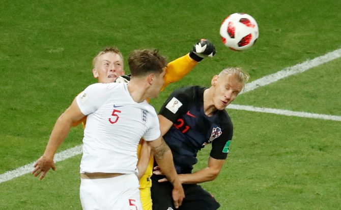 England's keeper Jordan Pickford punches the ball as he makes an aerial clearance