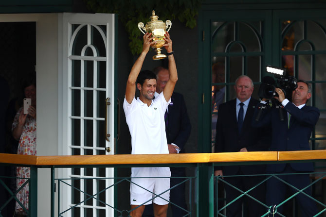 Novak Djokovic lifts the trophy on the balcony of Centre Court after winning the men's singles final against Kevin Anderson on day thirteen of the Wimbledon Lawn Tennis Championships at All England Lawn Tennis and Croquet Club in London, England, on Sunday