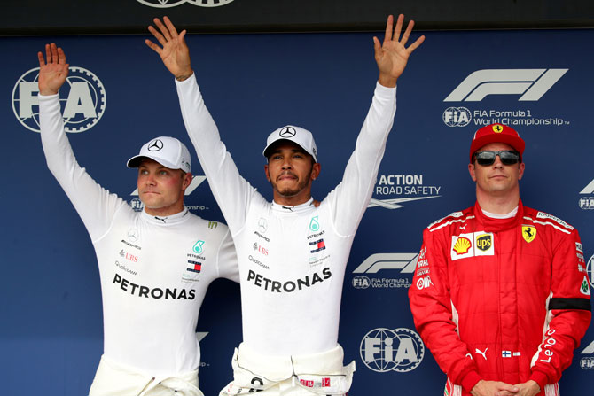 Mercedes' Lewis Hamilton (centre) celebrates after qualifying in pole position with second placed Mercedes' Valtteri Bottas (left) and third placed Ferrari's Kimi Raikkonen (right) after qualifying at the Hungarian F1 GP in Budapes on Saturday