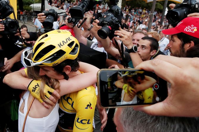 Team Sky rider Geraint Thomas of Britain, wearing the overall leader's yellow jersey, celebrates with his wife Sara Elen Thomas after the finish at the 116-km Stage 21 from Houilles to Paris Champs-Elysees on Sunday
