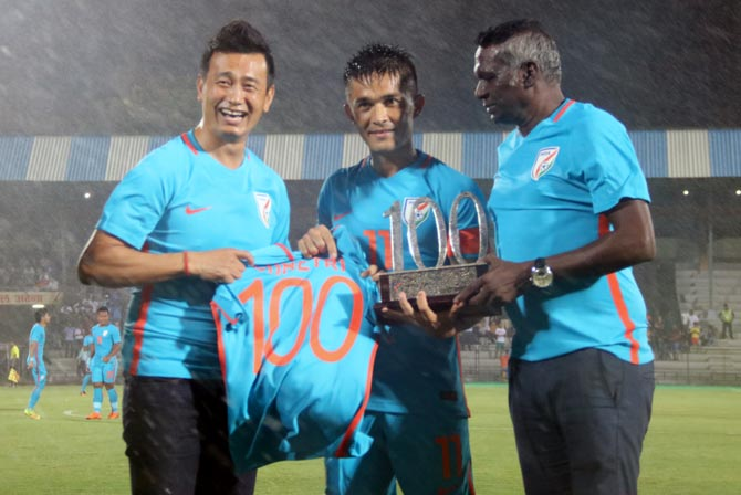 Indian football legends Bhaichung Bhutia, left, and I M Vijayan, right, present Sunil Chhetri with a trophy and a jersey to celebrate his 100th game for India. Photograph: AIFF Media