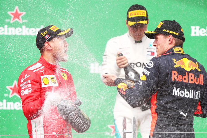 Race winner Sebastian Vettel of Germany and Ferrari and third place finisher Max Verstappen of Netherlands and Red Bull Racing celebrate on the podium after the Canadian Formula One Grand Prix at Circuit Gilles Villeneuve in Montreal, Canada, on Sunday