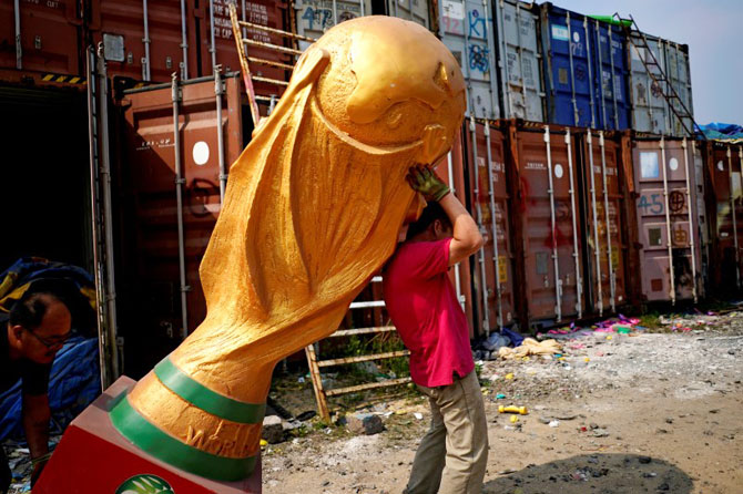 Workers work on a FIFA World Cup trophy replica at a small factory in the outskirts of Shanghai, China