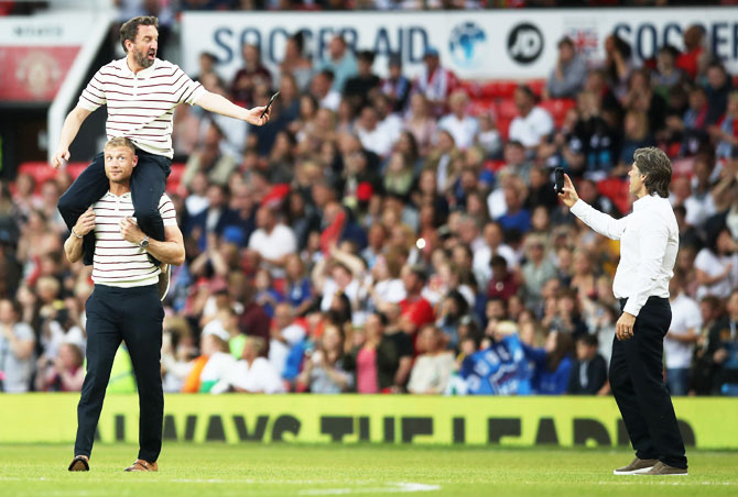 England's Lee Mack is carried by teammate Andrew Flintoff as John Bishop takes a photo prior to the Soccer Aid for UNICEF 2018 match