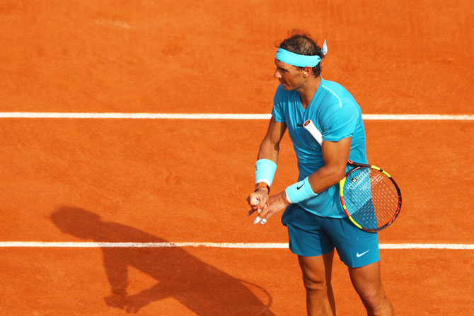 Rafael Nadal stretches his fingers following an injury during the French Open final