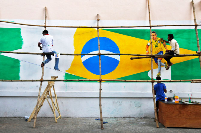 A painter applies finishing touches to an image of Brazil's Neymar, on a large Brazilian flag on a road side wall in Kolkata on June 9