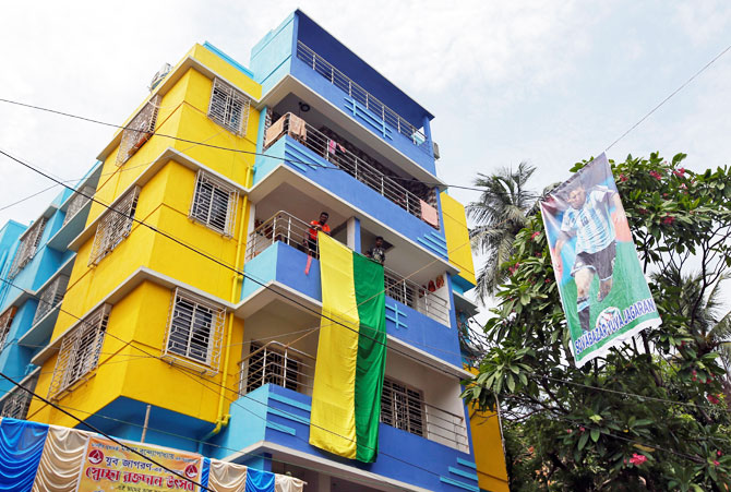 Fans hang a large flag from a residential building next to a banner featuring Argentina's soccer player Lionel Messi in Kolkata on June 10