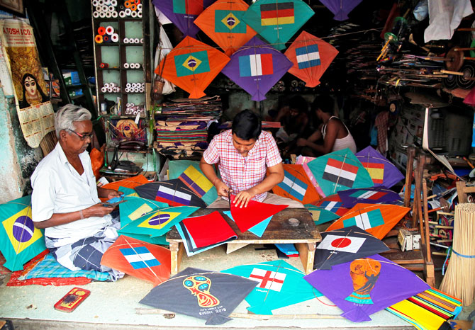 Kite-makers make kites with pictures of the national flags of the countries participating in the upcoming FIFA World Cup in Russia, at a workshop in Kolkata on June 5
