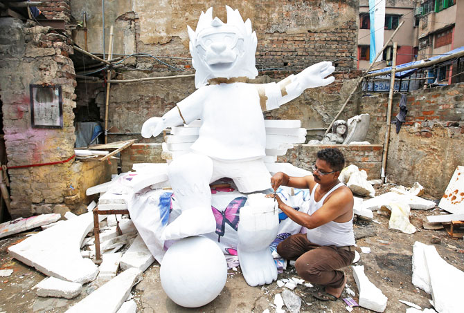 A man makes a replica of official mascot for the 2018 FIFA World Cup Russia at a workshop in Kolkata on June 11