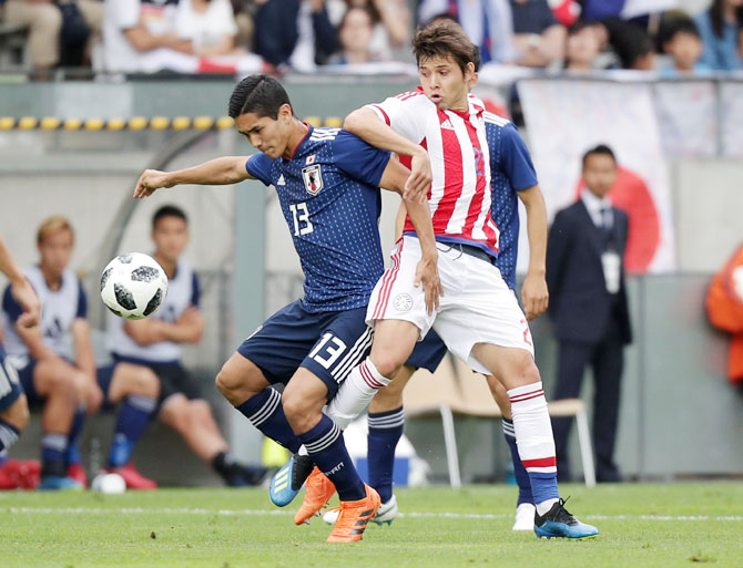 Japan's Yoshinori Muto in action with Paraguay's Oscar Romero vie for possession