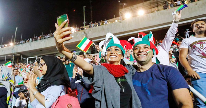 Iranian women are seen with their male friends, enjoying the FIFA World Cup match between Portugal and Iran on a big screen at Tehran's Azadi Stadium
