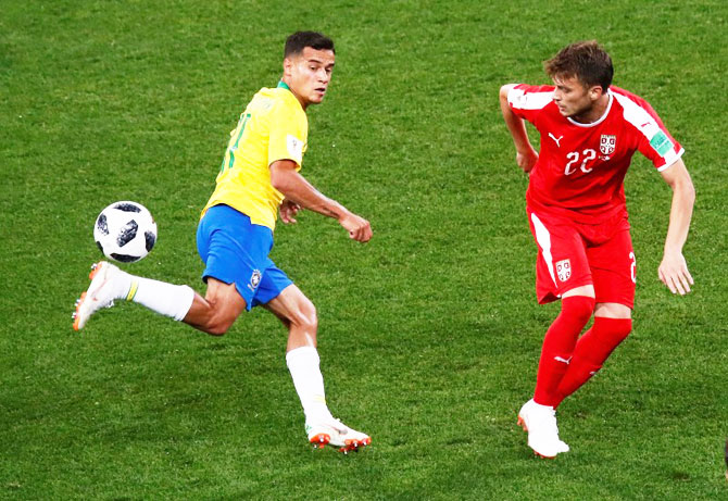 Brazil's Philippe Coutinho wins the ball in a challenge against Serbia's Adem Ljajic
