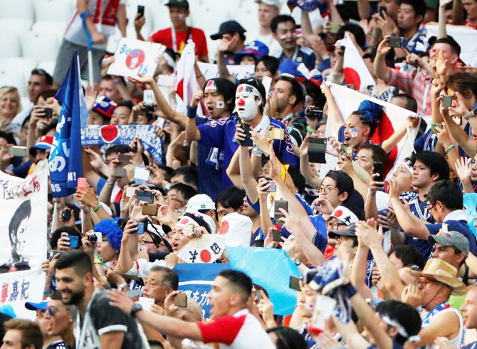 Japan fans celebrate after the match against Poland on Thursday