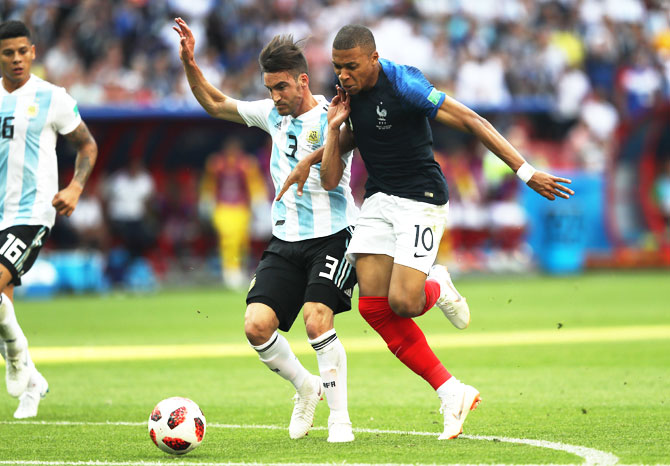 Argentina's Nicolas Tagliafico fouls France's Kylian Mbappe, leading to a free-kick outside the penalty area