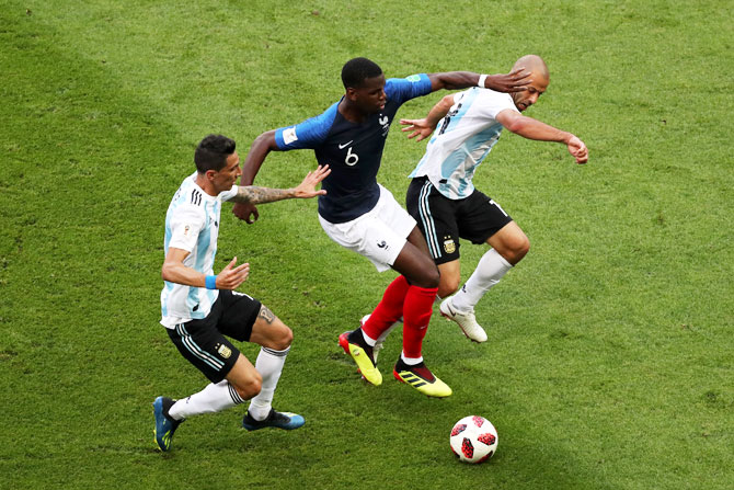 France's Paul Pogba is challenged by Argentina's Javier Mascherano and Angel Di Maria