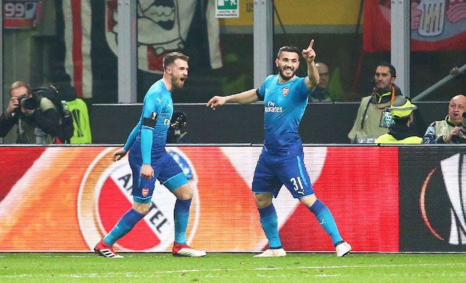 Arsenal's Aaron Ramsey celebrates with teammate Sead Kolasinac after scoring their second goal in the Europa League Round of 16 First Leg match at San Siro Stadium in Milan