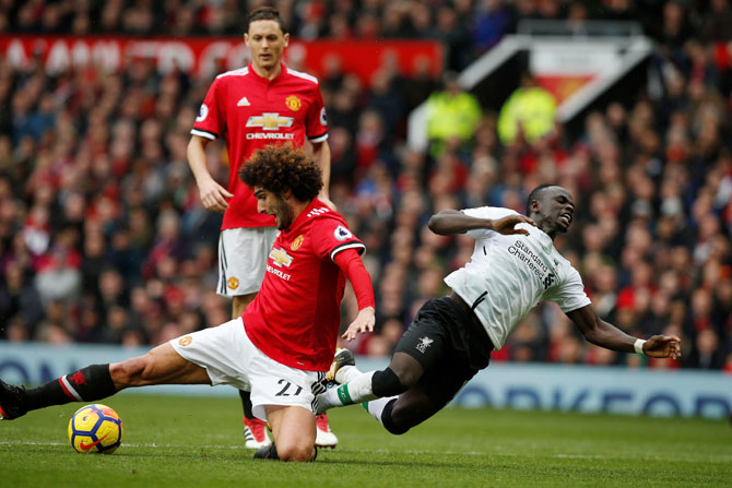 Manchester United's Marouane Fellaini in an ugly challenge with Liverpool's Sadio Mane