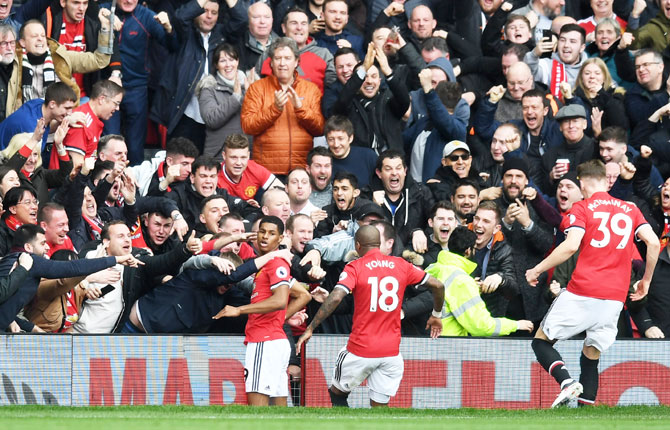 Manchester United's Marcus Rashford celebrates with fans and team mates after scoring the first goal against Liverpool during their Premier League match at Old Trafford in Manchester