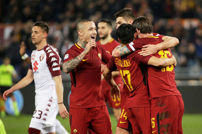 AS Roma's Daniele De Rossi celebrates with Radja Nainggolan and teammates after scoring their second goal against Torino in their Serie A match at Stadio Olimpico, Rome on Friday