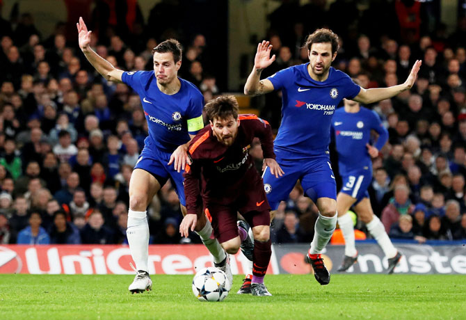 Barcelona's Lionel Messi is put under pressure by Chelsea's Cesar Azpilicueta and Cesc Fabregas