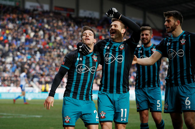 Southampton's Cedric Soares celebrates with Dusan Tadic and teammates after scoring their second goal against Wigan Athletic at DW Stadium, Wigan, on Sunday