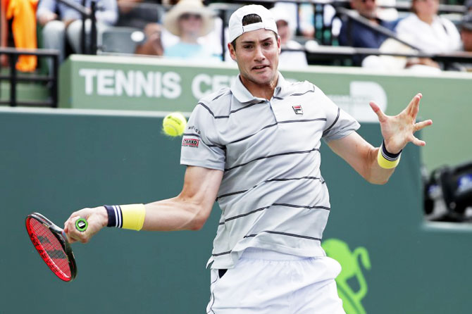 United States' John Isner hits a forehand against Korea's Hyeon Chung at Tennis Center at Crandon Park