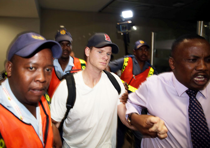 Axed Australian cricket captain Steve Smith is escorted by Police officers as he leaves the O.R. Tambo International Airport in Johannesburg on Wednesday