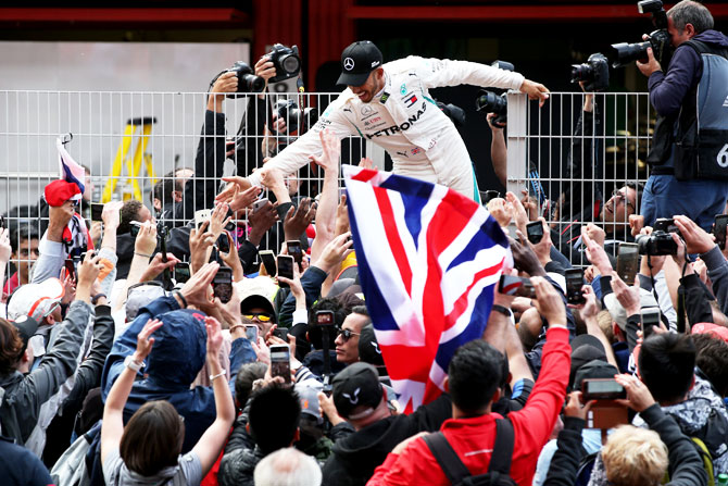 Mercedes GP's Lewis Hamilton celebrates with fans on the pit wall after winning the Spanish Formula One Grand Prix at Circuit de Catalunya in Montmelo, Spain, on Sunday