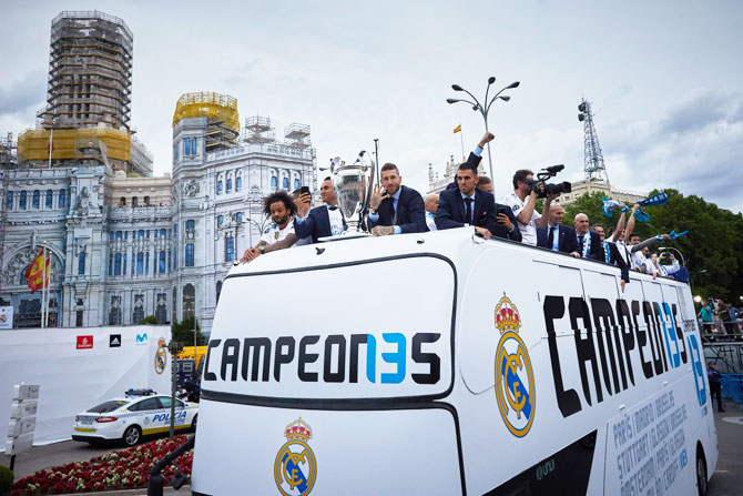 Real Madrid's captain Sergio Ramos (right) shows off the trophy to their fans with his teammate Marcelo (left) as they celebrate their Champions League trophy during the bus parade at Cibeles Square in Madrid on Sunday