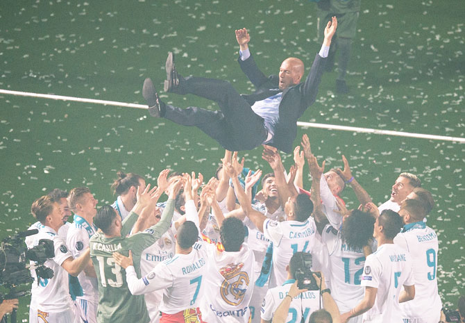 Real Madrid manager Zinedine Zidane is thrown in the air by his players during celebrations at the Santiago Bernabeu stadium on Sunday