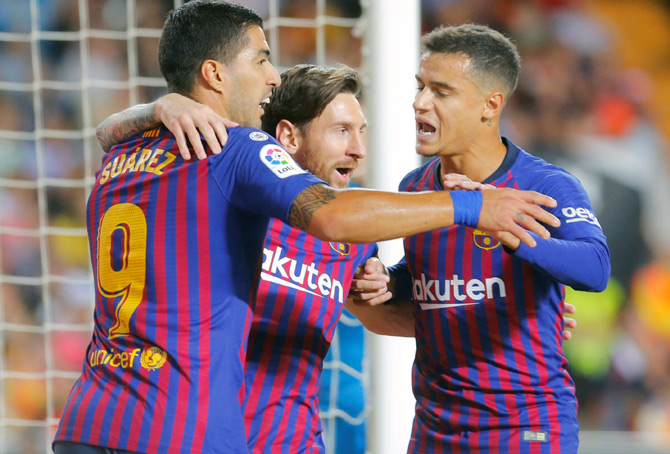 Lionel Messi, centre, celebrates scoring a goal for Barcelona with Luis Suarez, left, and Philippe Coutinho