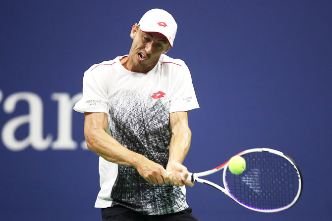 John Millman plays a return against Roger Federer