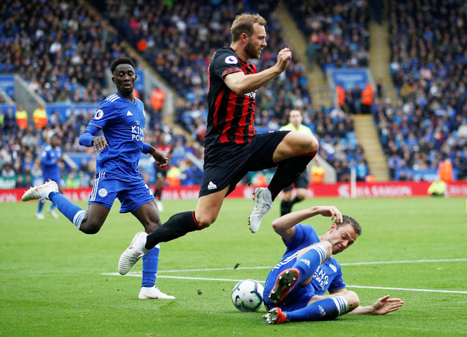Leicester City's Jonny Evans and with Huddersfield Town's Laurent Depoitre vie for possession