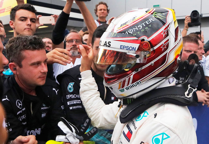 Lewis Hamilton celebrates with his team after winning the race