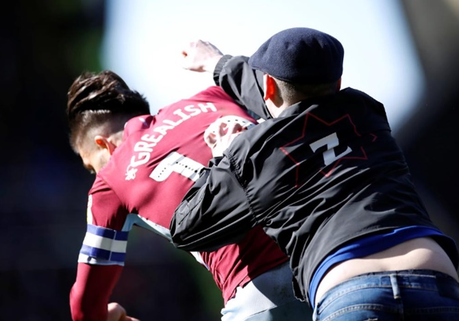 Aston Villa's Grealish is PUNCHED by pitch invader in derby win