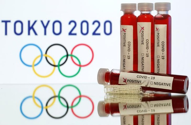 Fake blood in seen in test tubes labelled with coronavirus disease (COVID-19) in front of a displayed Tokyo 2020 Olympics logo in this illustration.