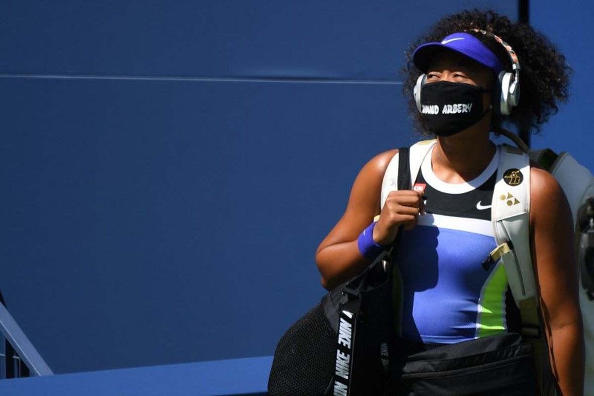 Naomi Osaka walks onto the court wearing a mask with the name of Ahmaud Arbery prior to her third round match against Ukraine's Marta Kostyuk (not pictured)