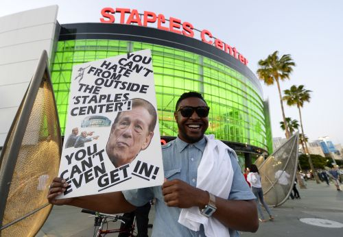 Protester holds a sign in front of the Staples Center in Los Angeles,