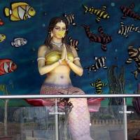 A facemask is put on a mermaid at Marine Drive