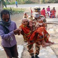 An elderly voter being carried to a poll station to cast her vote in Bihar