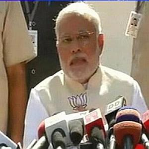 Modi in trouble with EC for flashing BJP symbol during presser