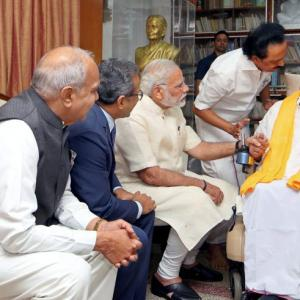 In show of warmth, Modi sits next to Karunanidhi, holds his hands
