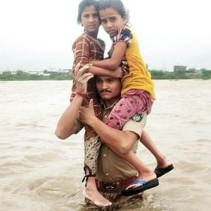Guj cop carries 2 children on shoulders in floodwater