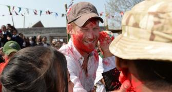 PHOTOS: Britain's Prince Harry sees red during Holi in Nepal