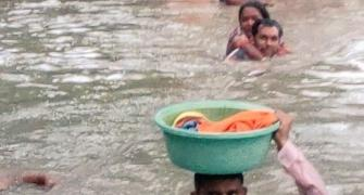 Cop carries baby in tub on his head in neck-deep water