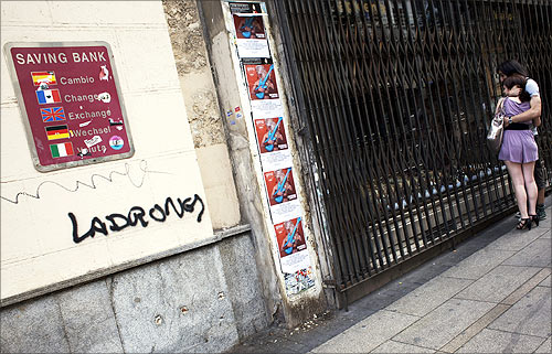 A couple looks at the window of a closed store next to graffiti that reads Thieves on the wall of the savings bank Cajastur in Madrid.