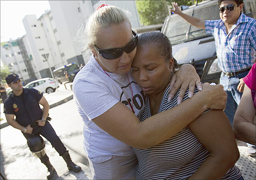 Josefina Florian Mendez (front R) is embraced by a supporter after she was evicted from her apartment in Madrid.