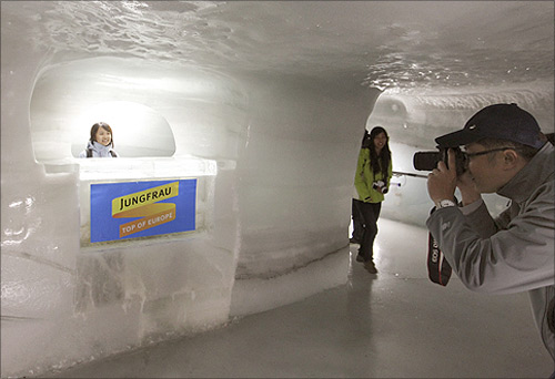A tourist poses for a pictures in the Ice Palace glacier cave at the Jungfraujoch (altitude 3454 metres/11333 feet).