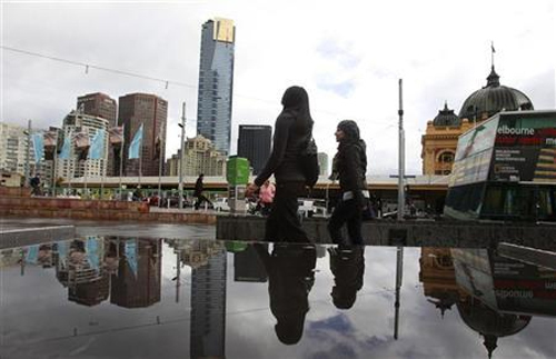 Office workers walk through Federation Square in Melbourne.